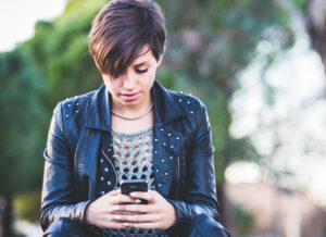 Girl wearing black leather jacket typing on smartphone