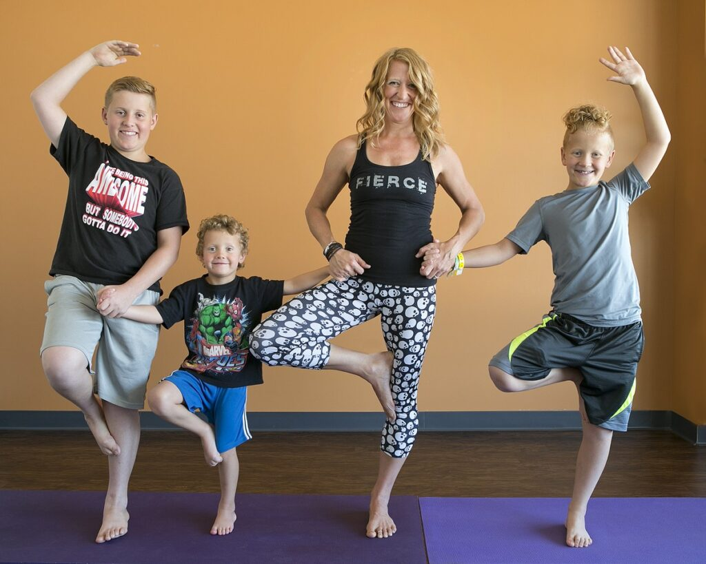 Yoga instructor and mother, Daina Lewis, Moline, stands strong with her children after successful spine fusion surgery at ORA Orthopedics. Daina is the owner of Shine! Yoga and Bodyworks, Moline.
